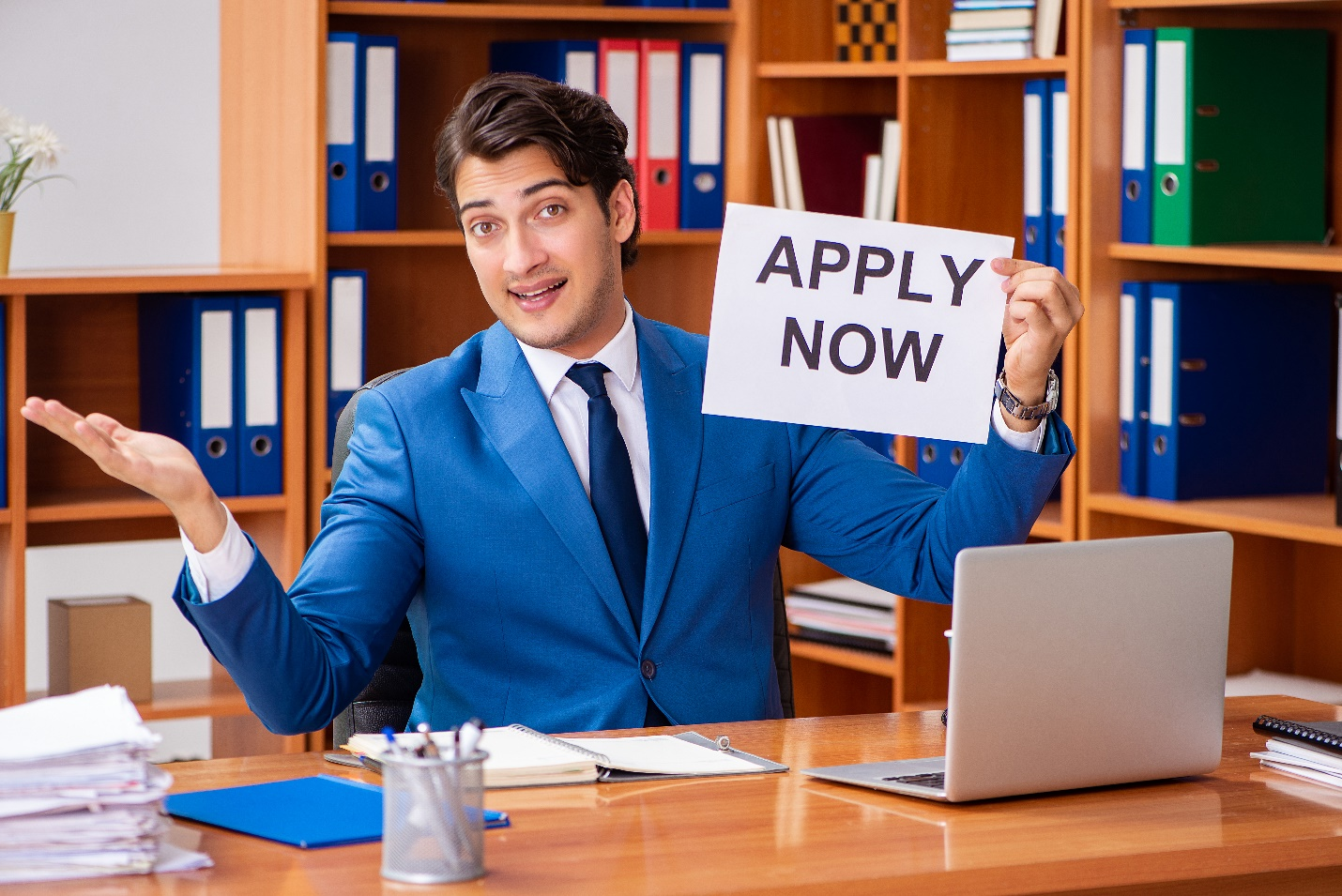A recruiter holding an 'Apply Now' sign
